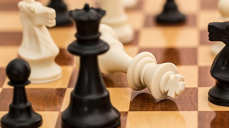 An image of a king toppled on a chess board