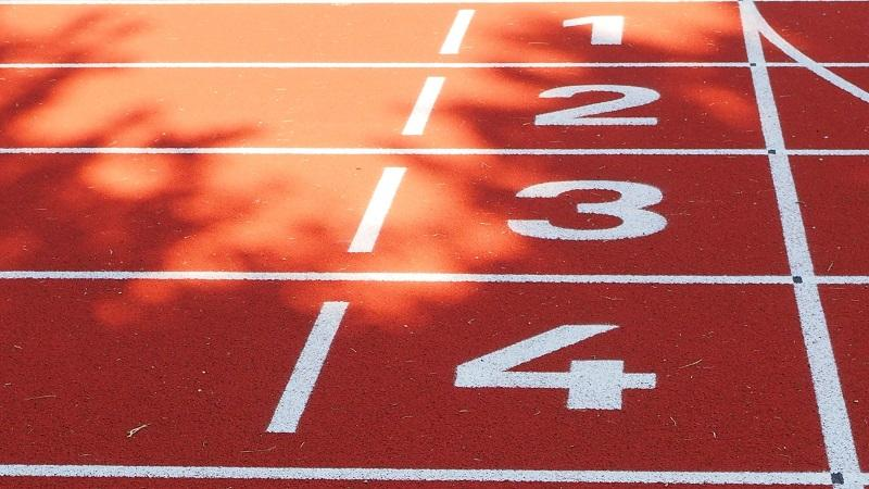 An image of the starting line for the first four lanes on a 100m running track