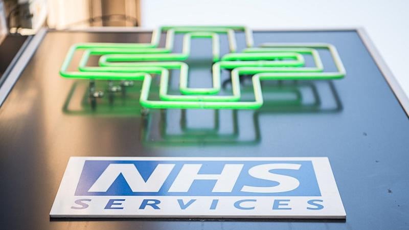 A close-up image of a green pharmacy sign on a wall above an 'NHS Services' sign
