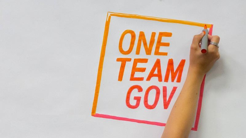 An image of someone finishing drawing the One Team Gov logo on a piece of paper