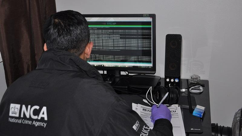 From-behind image of a National Crime Agency technical officer examining a seized computer for signs of criminal activity