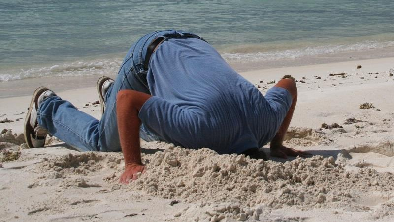An image of a man burying his head in the sand