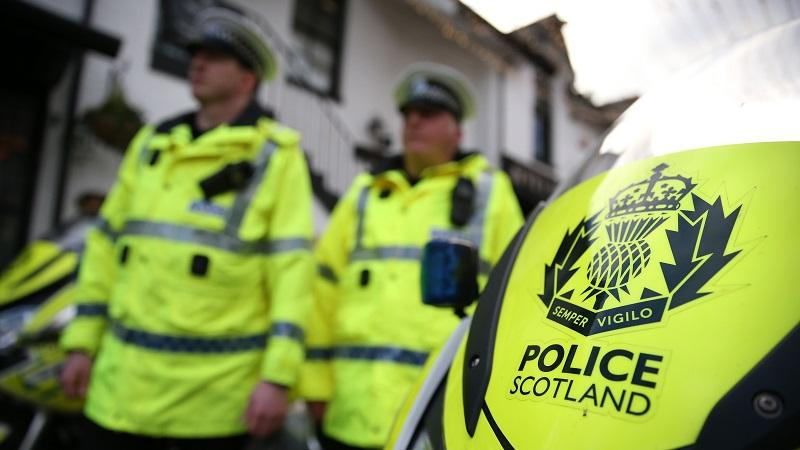 An image of two police officers with a motorbike displaying the 'Police Scotland' logo in the foreground