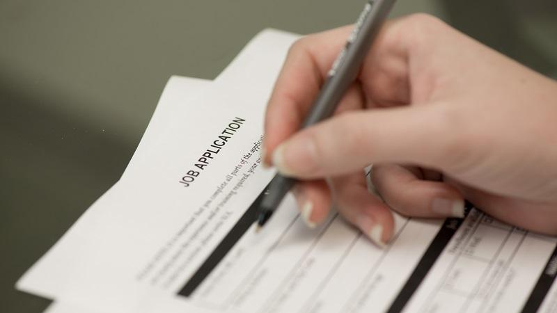 Close-up image of a person filling out a paper job application with a pen
