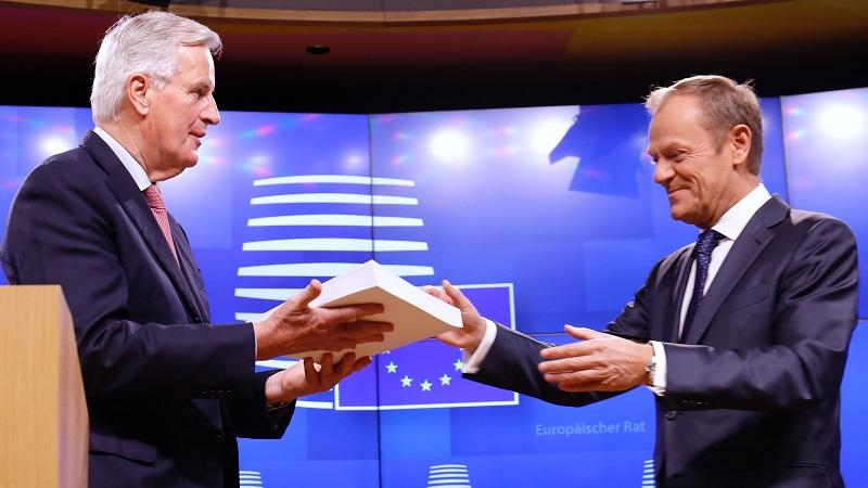 An image of the EU's chief Brexit negotiator Michel Barnier handing a paper copy of the draft withdrawal agreement to European Council president Donald Tusk