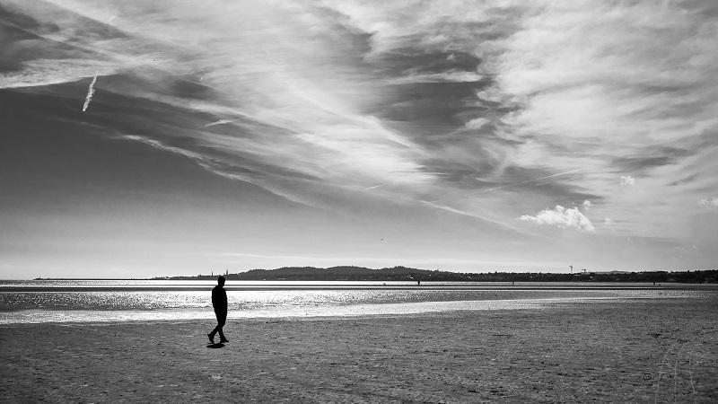An image of a man walking alone on a beach