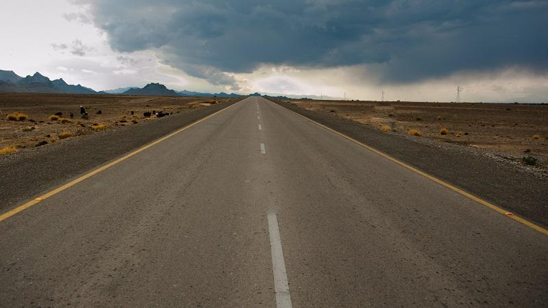 An image of a long, empty road stretching out into the distance