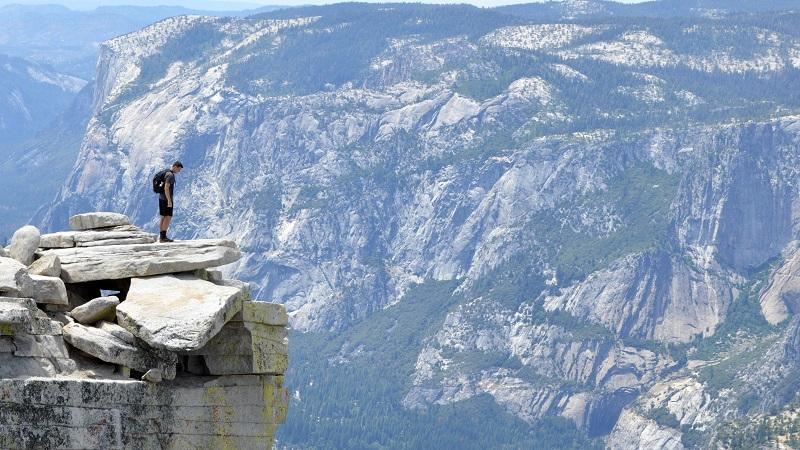An image of a man looking over cliffs at Yosemite National Park