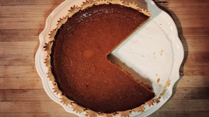 An overhead image of a pumpkin pie with a large slice missing