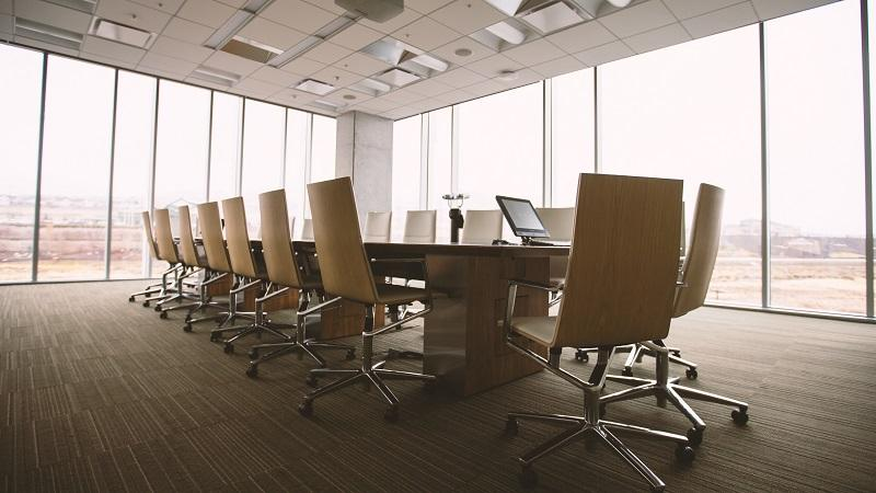 An image of an empty boardroom, with and large plate windows