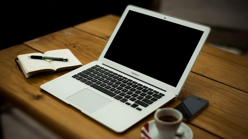 An image of a laptop on a wooden table next to a mobile phone, note pad, and espresso coffee