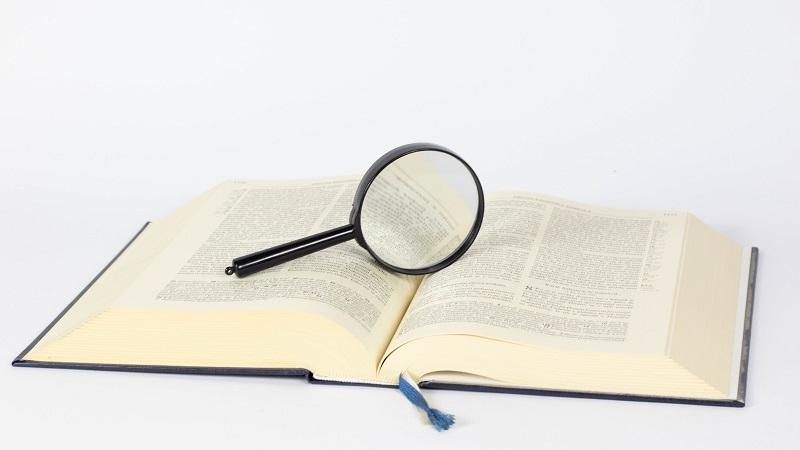 An image of an open book with a magnifying glass laid atop