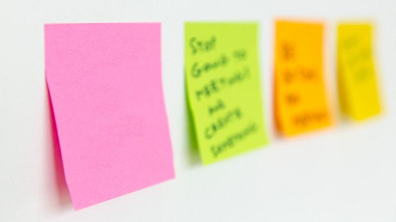 An image of four post it notes stuck to a wall - the further three are blurred and the nearest one is blank