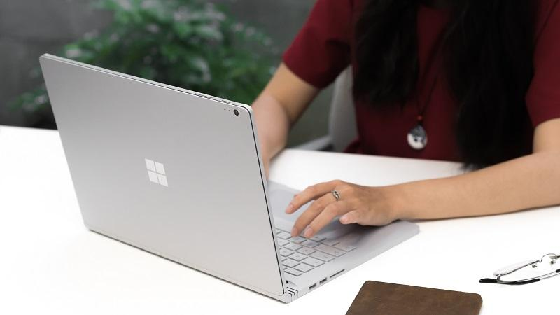 An image of a woman using a Microsoft Surface Book 2 2-in-1 device