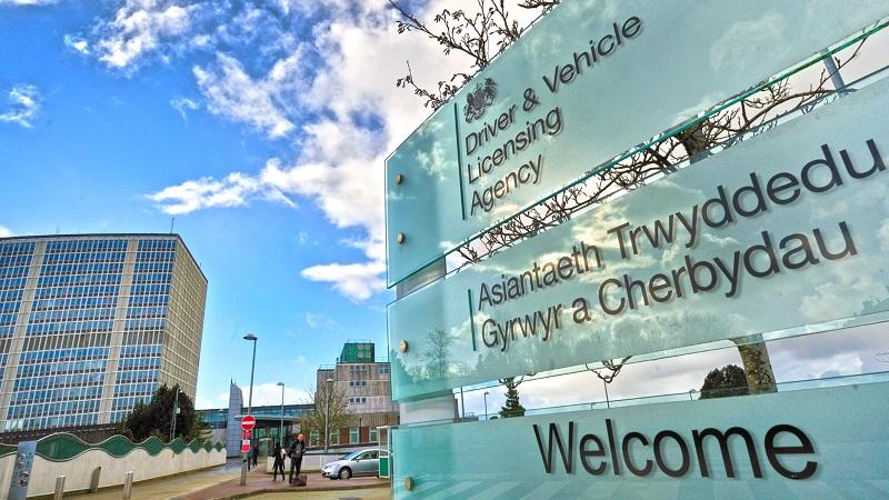 A close up image of the sign outside the DVLA's headquarters in Swansea, with the office in the background