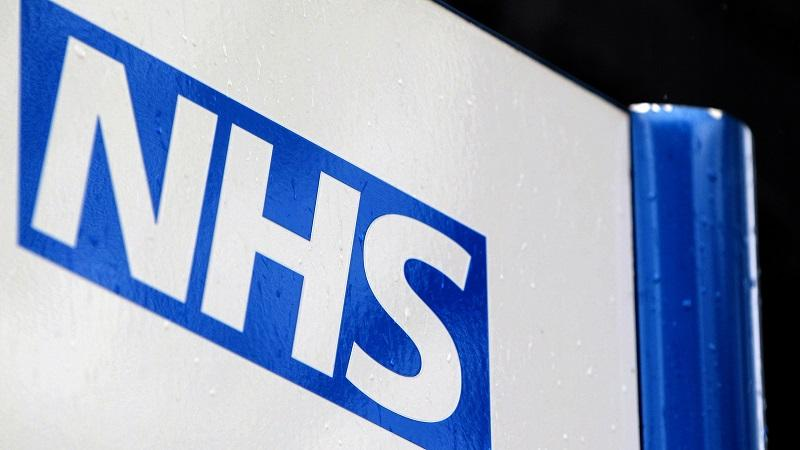 A close-up of the NHS logo on a sign