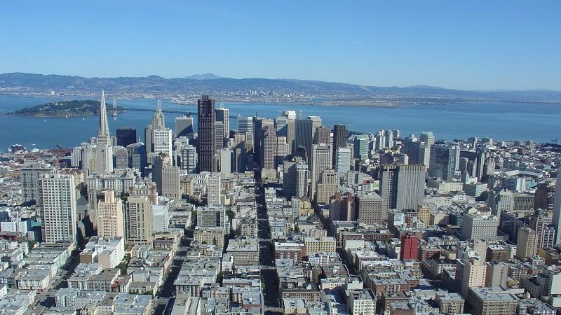An aerial image of the buildings of downtown San Francisco, with San Francisco bay in the background