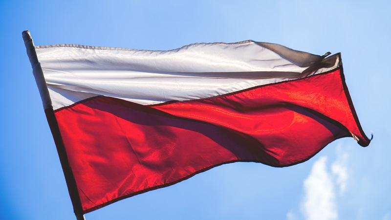 A close-up image of the Polish flag fluttering in the wind against a sunny blue sky