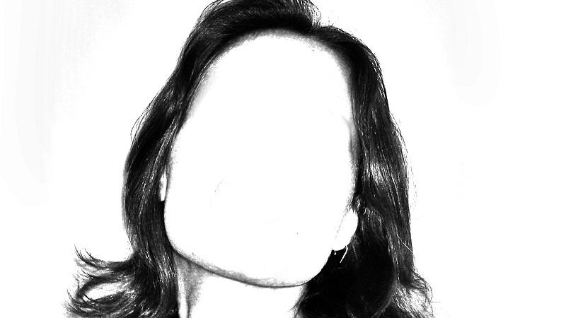 A black and white image of a woman with a blank space where her face would otherwise be