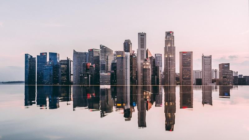 An image of Singapore's skyline at dusk mirrored by a reflection in water