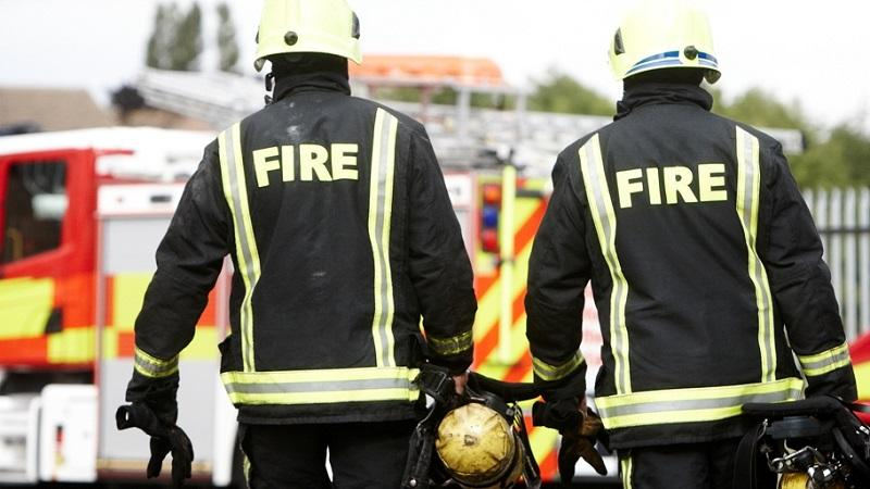 An image of two firefighters walking towards their fire engine