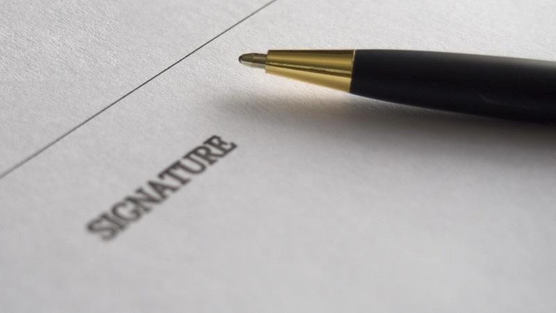 A close-up image of a pen lying on a piece of paper next to a space intended for a signature