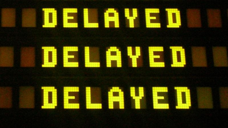A close-up of an airport departures board with the word 'delayed' featured three times