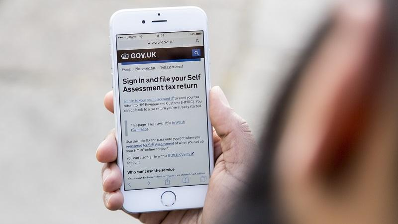 An image of a man holding up a mobile phone displaying a webpage for completing a self-assessment tax return on GOV.UK