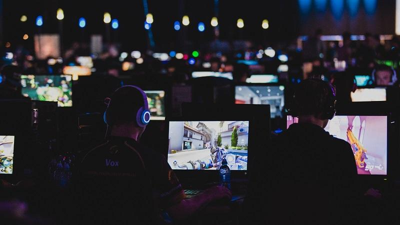 An image of rows of competitive gamers playing PC games in a  large, darkened room