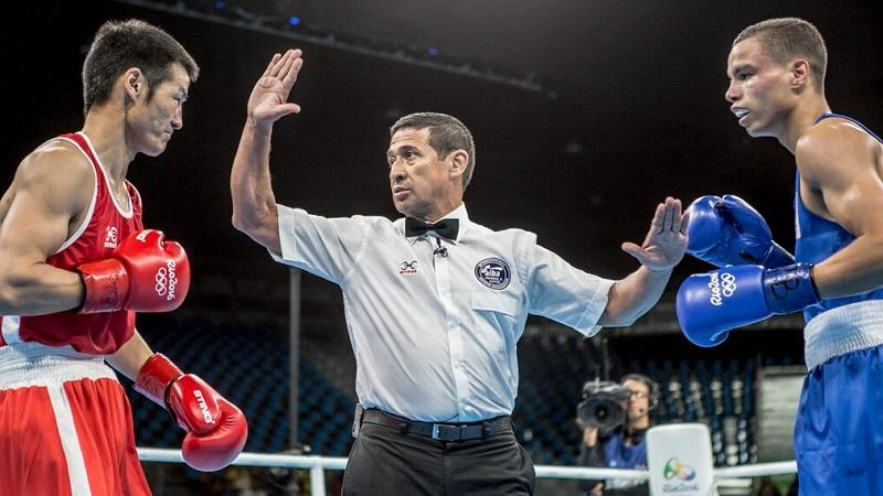 An image of a boxing referee standing between two fighters during a contest at the Rio 2016 Olympics