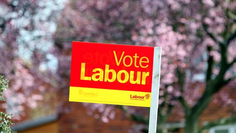 An image of a 'Vote Labour' sign standing in a voter's front garden