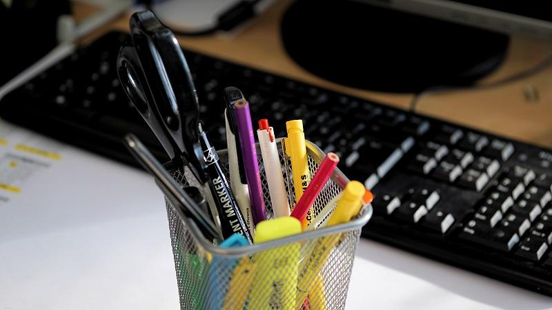 Pens and pencils in a container on a office desk with a keyboard in the background