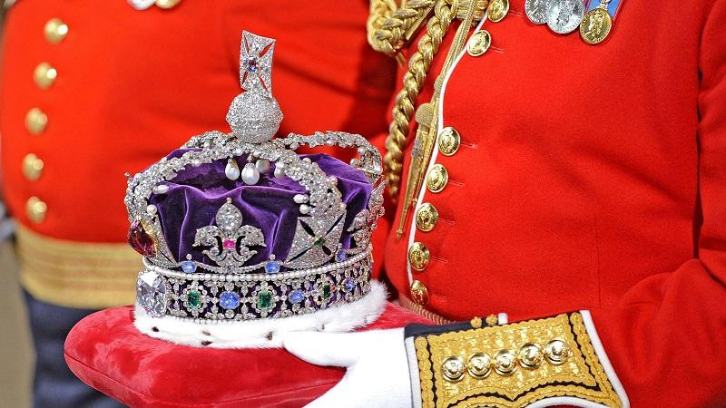 An image of the monarch's crown being carried on a cushion