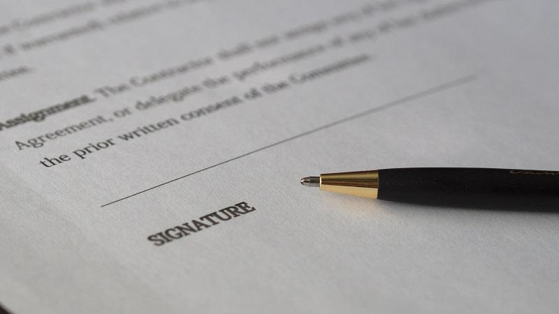 An image of a pen and a contract awaiting a signature