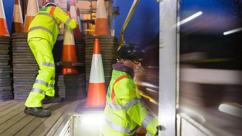 An image of two Highways England workers working from a truck laying cones