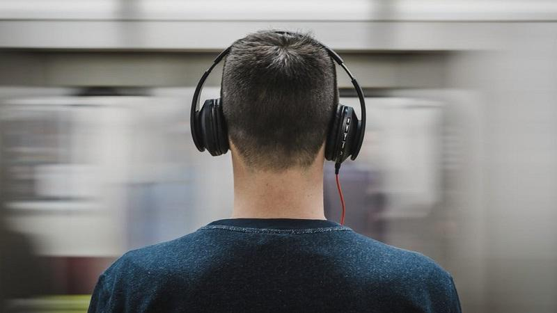 An image, shot from behind, of a man wearing headphones