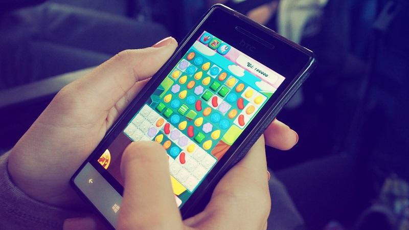 A close-up image of someone playing Candy Crush Saga on a smartphone