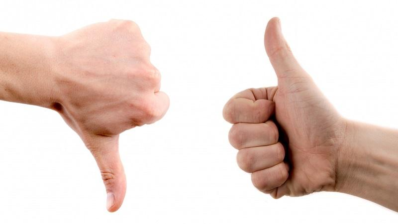 A close-up image of someone giving a thumbs down gesture and someone else giving a thumbs up