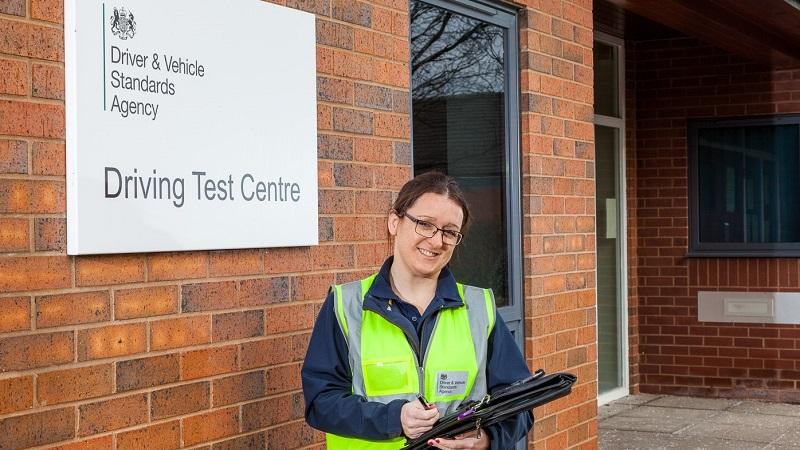 A driving examiner standing outside a DVSA test centre