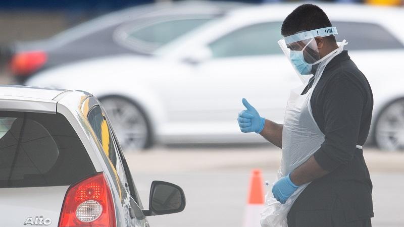 An image of a coronavirus tester at a drivethrough site wearing PPE kit
