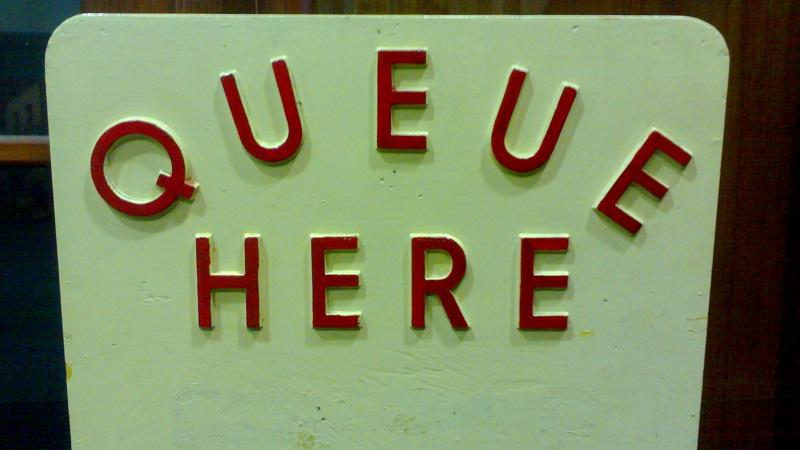 An image of a sign reading 'Queue here'