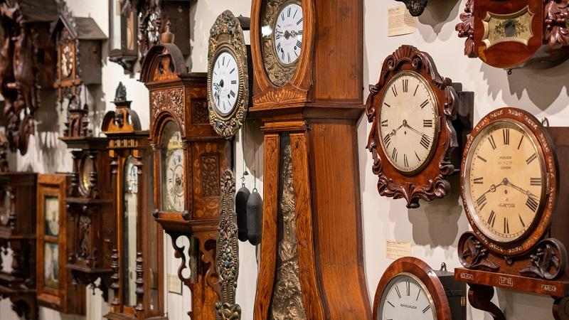 An image of numerous old clocks hanging on a wall