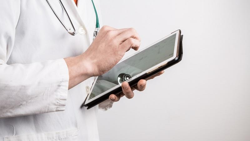 A close-up image of a doctor using a tablet