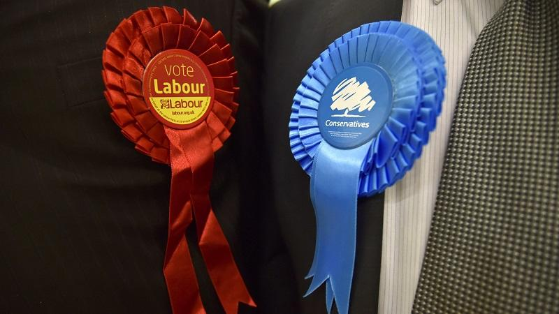 A close-up image of Labour and Conservative rosettes work on two people's lapels