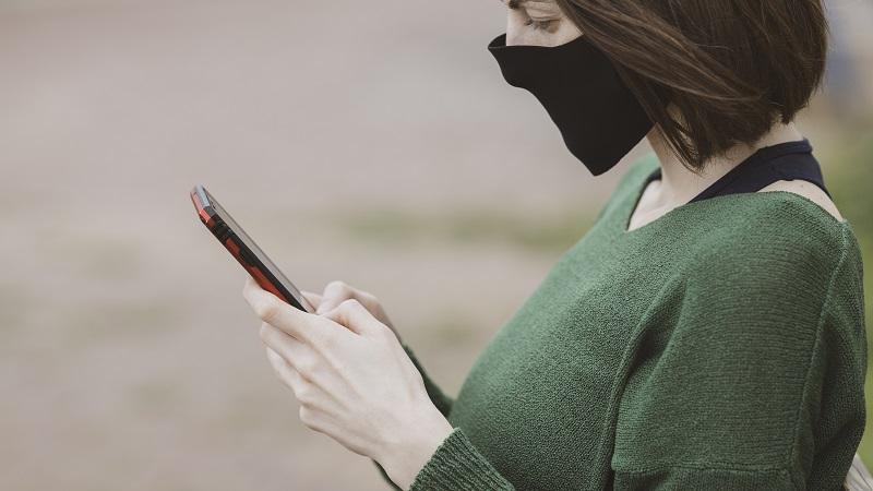 An image of a woman in a face mask looking at her phone