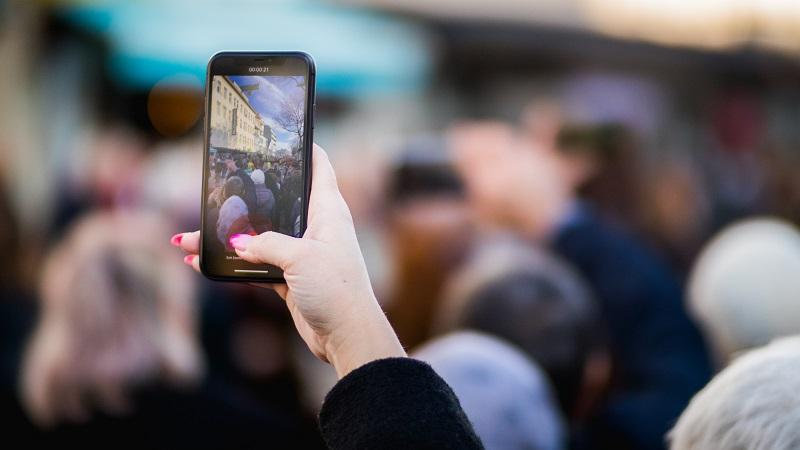 An image of a woman's hand raised above a crowd holding a phone that is recording