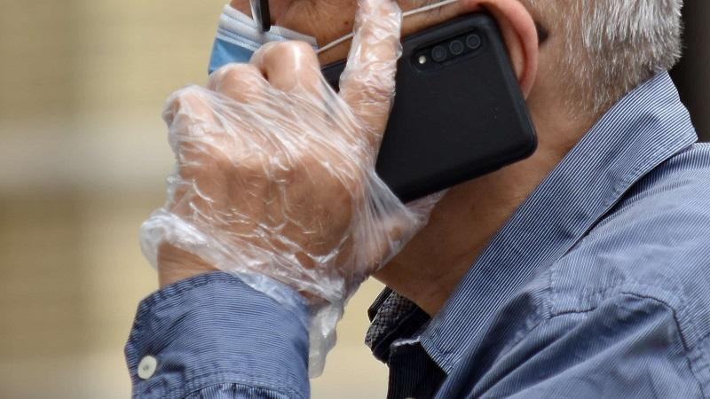 A close-up image of a man in a face mask and plastic gloves talking on a mobile phone