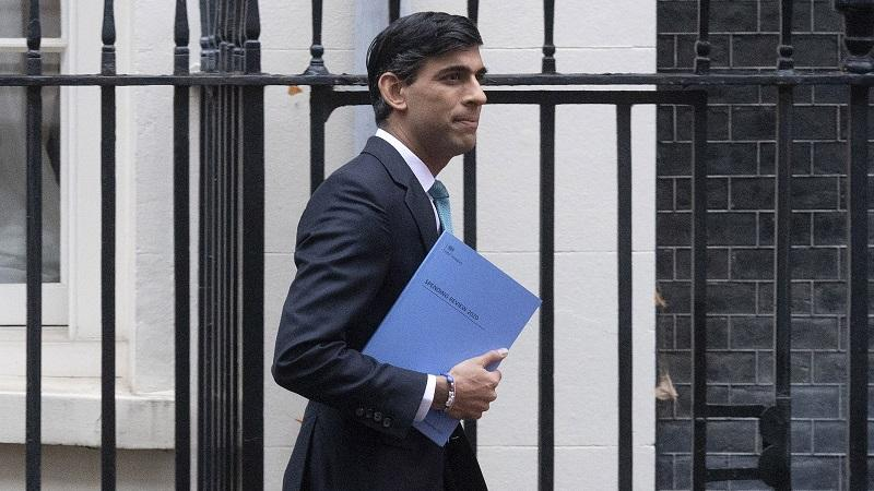An image of chancellor Rishi Sunak holding a copy of the 2020 spending review