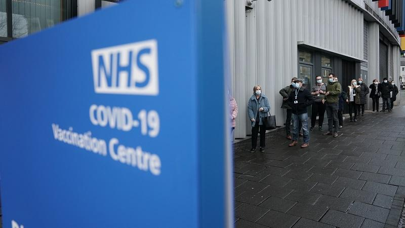 An image of people queueing outside a covid-19 vaccination centre