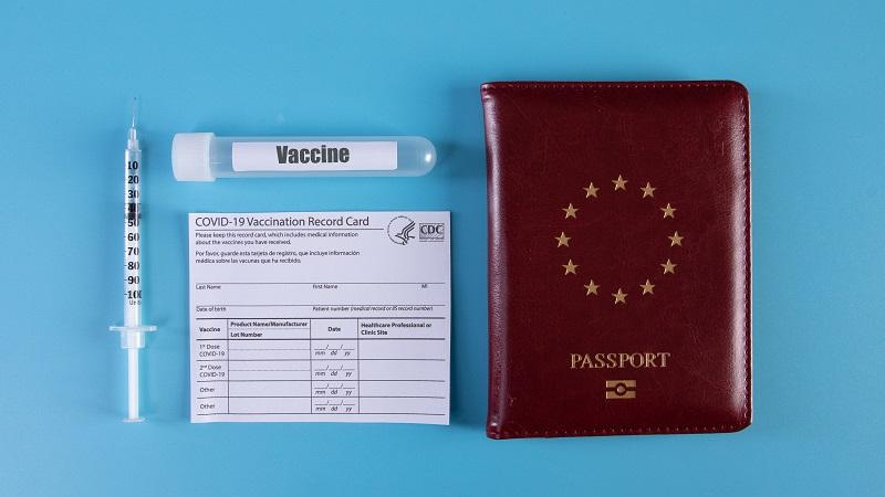 An image of a passport lying next to a vaccine tube and needle and a Covid-19 vaccination card